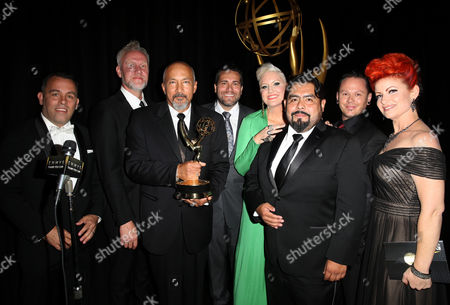 """Mike Mekash, from left, Christopher Allen Nelson, David LeRoy Anderson, James MacKinnon, Eryn Krueger Mekash, Luis García, Justin Raleigh and Kim Ayers pose backstage with award for outstanding prosthetic makeup for a series, limited series, movie or a special for """"American Horror Story: Freak Show"""" at the Television Academy's Creative Arts Emmy Awards at Microsoft Theater, in Los Angeles"""