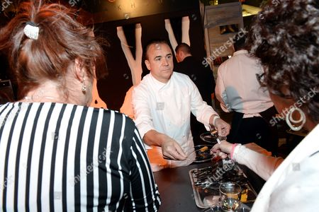 """Stock Photo of Chef Jean-Georges Vongerichten serves a guest at """"The Grand Tasting"""" during Vegas Uncork'd by Bon Appetit, presented by Chase Sapphire Preferred, at The Garden of The Gods, Caesars Palace, in Las Vegas"""
