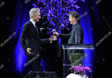 Sean Penn, right, presents the Media Social Visionary Award to John Sykes on stage at unite4:good and Variety's unite4:humanity at Sony Pictures Studios, in Culver City, Calif
