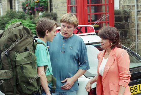 Stock Image of Ep 2114 Tuesday 10th September 1996  Scott says goodbye to Vic as he leaves for the Army. Vic is still not very supportive of him and tries to tell Scott that he is proud of him, but he can't quite bring himself to give him a hug. Scott and Viv leave in a taxi - With Viv Windsor, as played by Deena Payne ; Vic Windsor, as played by Alun Lewis ; Scott Windsor, as played by Toby Cockerell.