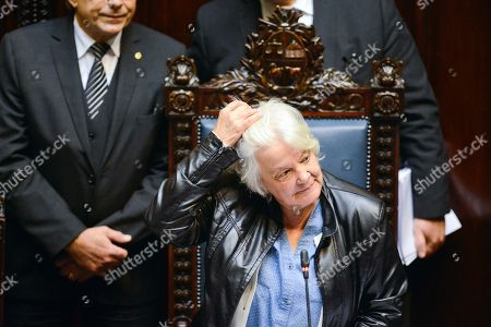 Uruguay's newly named Vice President Lucia Topolansky pushes back her hair as she presides over a session in Senate chambers, in Montevideo, Uruguay, . Vice President Raul Sendic resigned Wednesday amid allegations of corruption and was replaced by Topolansky, the first woman in Uruguay to hold that position