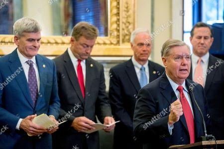 Lindsey Graham, Bill Cassidy, Ron Johnson, Dean Heller, Rick Santorum. From left, Senator Bill Cassidy, R-La., Senator Dean Heller, R-Nev., Senator Ron Johnson, R-Wis., Senator Lindsey Graham, R-S.C., and former Senator Rick Santorum, R-Pa., hold a press conference on Capitol Hill in Washington, to unveil legislation to reform health care