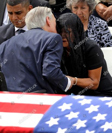 Stock Picture of Texas Gov. Greg Abbott, left, hugs Cheryl Perez during a funeral service for her husband, Houston Police Sgt. Steve Perez, in Houston. Sgt. Perez drowned last month after being trapped in Hurricane Harvey-related flooding while driving to work