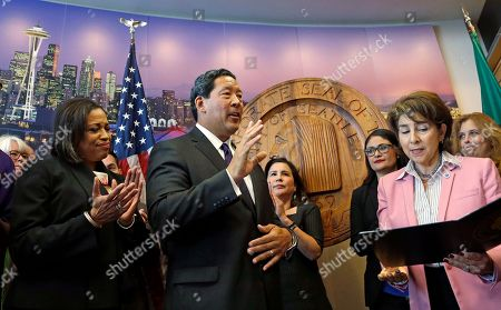 New Seattle Mayor Bruce Harrell, center, gives a wave after taking the oath of office for mayor from City Clerk Monica Martinez Simmons, right, as his wife Joanne Harrell looks, in Seattle. Harrell, who was City Council president, assumed the temporary position following the resignation of Ed Murray