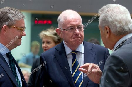 European Commissioner for Migration Dimitris Avramopoulos, right, and European Commissioner for the Security Union Julian King, left, speak with Irish Justice Minister Charles Flanagan during a meeting of EU interior ministers at the Europa building in Brussels on . The EU's top migration official said Thursday that extraordinary border controls inside Europe's passport-free travel area should not be extended because the refugee emergency is abating