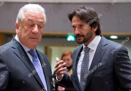 European Commissioner for Migration Dimitris Avramopoulos, left, speaks with Slovak Interior Minister Robert Kalinak during a meeting of EU interior ministers at the Europa building in Brussels on . The EU's top migration official said Thursday that extraordinary border controls inside Europe's passport-free travel area should not be extended because the refugee emergency is abating