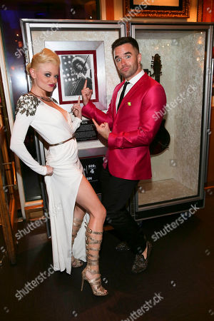 """From left, cast members Ruby Lewis and Brian Justin Crum pose with a photo of Brian May during the party for the opening night performance of Queen and Ben Elton's """"We Will Rock You"""" at the Center Theatre Group/Ahmanson Theatre, in Los Angeles, Calif"""