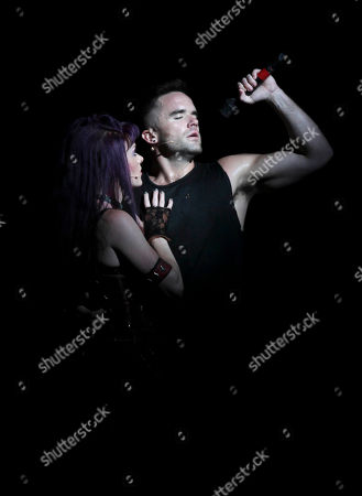 """From left, cast members Ruby Lewis and Brian Justin Crum sing during the party for the opening night performance of Queen and Ben Elton's """"We Will Rock You"""" at the Center Theatre Group/Ahmanson Theatre, in Los Angeles, Calif"""