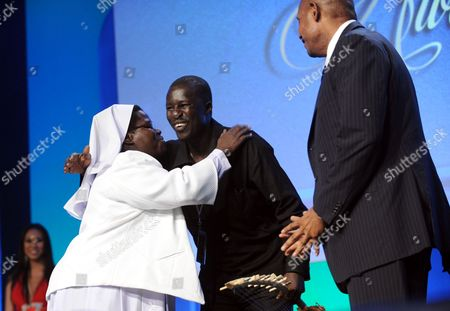 "Sister Rosemary Nyirumbe hugs Okello Sam as Forrest Whitaker watches at the 12th Annual Starkey Hearing Foundation ""So The World May Hear"" Gala on in St. Paul, Minnesota"
