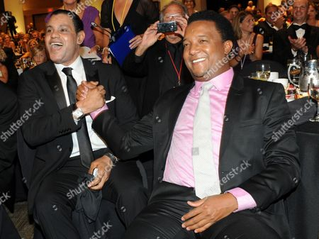 "Sammy Sosa and Pedro Martinez celebrate having the winning bid for a guitar signed by Glenn Frey of the Eagles at the 12th Annual Starkey Hearing Foundation ""So The World May Hear"" Gala on in St. Paul, Minn. The foundation conducts dozens of hearing missions every year in the U.S. and around the world and has given the gift of hearing in more than 97 countries"