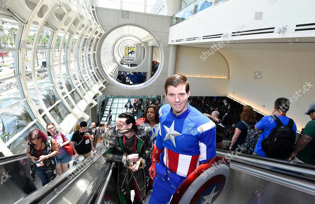 Stock Photo of Matt Rogers, dressed as Captain America, rides the escalator up on day 1 of the 2014 Comic-Con International Convention held in San Diego