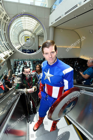 Stock Picture of Matt Rogers, dressed as Captain America, rides the escalator up on day 1 of the 2014 Comic-Con International Convention held in San Diego