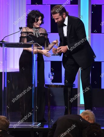 Bradley Cooper, right, presents the Sid Grauman award to Sue Kroll at the 30th annual American Cinematheque Award at the Beverly Hilton Hotel, in Beverly Hills, Calif