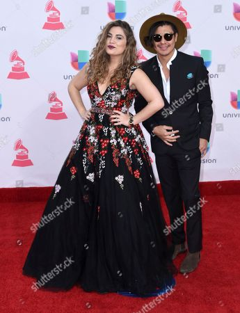 Jessi Leon, left, and Periko arrive at the 17th annual Latin Grammy Awards at the T-Mobile Arena, in Las Vegas
