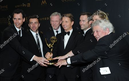 Bradley Bell, center, and the crew of The Bold and the Beautiful pose in the pressroom with the award for outstanding writing in a drama series for The Bold and the Beautiful at the 43rd annual Daytime Emmy Awards at the Westin Bonaventure Hotel, in Los Angeles