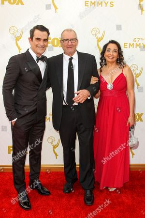 From left, Ty Burrell, Ed O'Neill, and Catherine Rusoff arrive at the 67th Primetime Emmy Awards, at the Microsoft Theater in Los Angeles