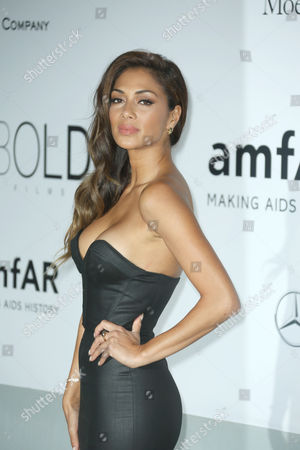 Singer Nicole Sherzinger poses for photographers as she arrives at the amfAR Cinema Against AIDS benefit at the Hotel du Cap-Eden-Roc, during the 67th international film festival, in Cap d'Antibes, southern France