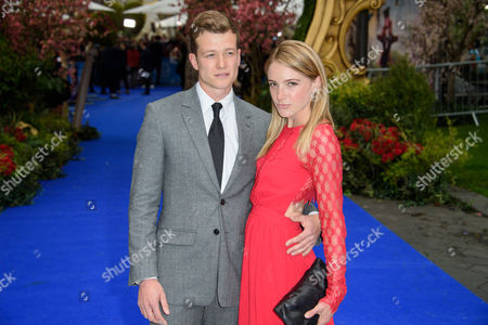 Ed Speleers and Asia Macey pose for photographers upon arrival at the European premiere of the film 'Alice Through The Looking Glass' at a central London cinema, London