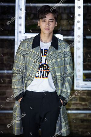 Li Yifeng poses for photographers upon arrival at the Stella McCartney collection presentation, in London