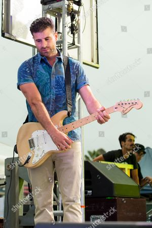 Guitaris Mark Pellizzer of the band Magic! performs on stage during the Pandora Presents The 2014 Summer Party at The Santa Monica Pier, in Santa Monica, Calif