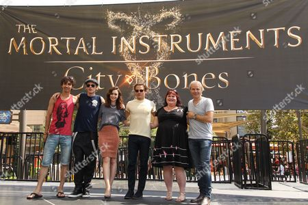 """Stock Image of From left, actors Robert Sheehan, Jamie Campbell Bower, Lily Collins, Kevin Zegers, novelist Cassandra Clare, and director Harald Zwart attend the """"The Mortal Instruments: City of Bones"""" meet and greet at The Americana on in Glendale, Calif"""