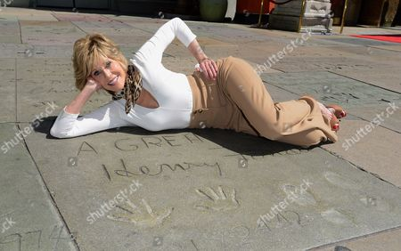 Jane Fonda poses in front of her father, Henry Fonda's hand and footprint as the 2013 TCM Classic Film Festival honors Jane Fonda with a handprint and footprint ceremony at the TCL Chinese Theatre on in Los Angeles