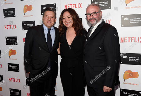 """Pioneer Award recipient Ted Sarandos, left, head of content acquisition for Netflix, Liz Garbus, center, director of the documentary film """"What Happened, Miss Simone?"""", and Simon Kilmurry, executive director of the International Documentary Association, pose together at the 2015 IDA Documentary Awards at Paramount Studios, in Los Angeles"""