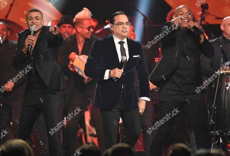 """Gilberto Santa Rosa, center, performs """"Aguanile"""" with Randy Malcom Martinez, left, and Alexander Delgado, of Gente De Zona, at the Latin Recording Academy Person of the Year Tribute honoring Marc Anthony at the MGM Grand Garden Arena, in Las Vegas"""