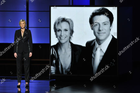 Jane Lynch presents a tribute to Cory Monteith, who is seen on screen at right at the 65th Primetime Emmy Awards at Nokia Theatre, in Los Angeles