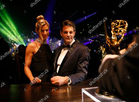 """Lee Metzger, right, poses with the award for outstanding reality-competition program for """"the Voice,"""" and guest attend the Governors Ball for the 68th Primetime Emmy Awards at the Los Angeles Convention Center, in Los Angeles"""