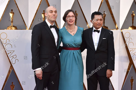 Stock Image of Joshua Oppenheimer, from left, Signe Byrge Sorensen and Adi Rukun arrive at the Oscars, at the Dolby Theatre in Los Angeles