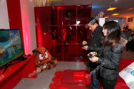 Mario Lopez, left, and Courtney Laine Mazza warm up and check out Wii U at the Nintendo Lounge while playing Nintendo Land during a break from the Sundance Film Festival on in Park City, UT
