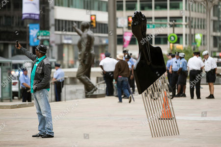 A man takes a selfie with Hank Willis Thomas' All Power to All People sculpture in view of a statue of former Philadelphia mayor and police commissioner Frank Rizzo in Philadelphia, . Mural Arts Philadelphia installed the sculpture, which has a black handle topped by a clenched fist, as part of Monument Lab, an initiative to create public works about issues such as social justice and gentrification