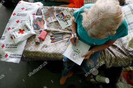 Kudy Ann Bell spends her time coloring at a special needs shelter, at Florida International University in Miami, Fla. About 30 people, including staff with the Florida Keys Outreach Coalition for the Homeless from Key West, Fla., were sheltered in a storefront underneath a parking garage on campus