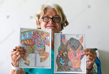 Kudy Ann Bell shows off some of the pictures she has coloring while spending time at a special needs shelter, at Florida International University in Miami, Fla. About 30 people, including staff with the Florida Keys Outreach Coalition for the Homeless from Key West, Fla., were sheltered in a storefront underneath a parking garage on campus