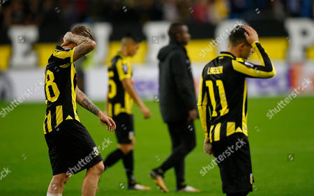 Vitesse team members Vitesse's Bryan Linssen, right, and Vitesse's Alexander Buttner, left, walk off the pitch after losing a Europa League group K soccer match between Vitesse and Lazio at the Gelredome Arena in Arnhem, Netherlands, on