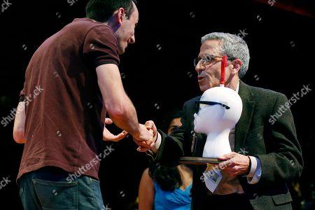 Marc-Antoine Fardin, left, accepts his Ig Nobel Physics Prize from Nobel laureate Eric Maskin during ceremonies at Harvard University in Cambridge, Mass