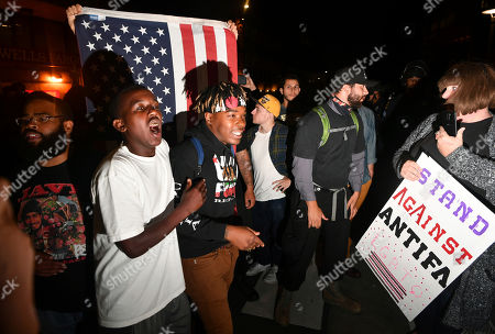 Amber Cummings, right, holds a sign as Phoenix Jones, in white shirt, and Morris Black, center, shout during a protest outside of a speaking engagement by Ben Shapiro on the campus of the University of California Berkeley in Berkeley, Calif., . Several streets around the University of California, Berkeley, were closed off Thursday with concrete and plastic barriers ahead of an evening appearance by the conservative commentator - the latest polarizing event to raise concerns of violence on the famously liberal campus