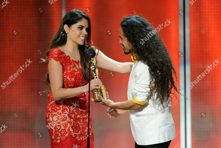 Yarel Ramos, left, presents Ruben Albarran of the musical group Cafe Tacuba with the de tu mundo award on stage at the NCLR ALMA Awards at the Pasadena Civic Auditorium, in Pasadena, Calif