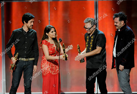 Yarel Ramos, second from left, presents Emmanuel del Real, Joselo Range, and Enrique Rangel of the musical group Cafe Tacuba with the de tu mundo award on stage at the NCLR ALMA Awards at the Pasadena Civic Auditorium, in Pasadena, Calif