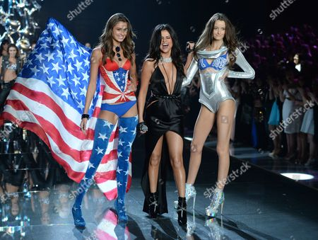 Taylor Hill, left, and Megan Puleri, right, walk the runway as Selena Gomez, center, performs during the Victoria's Secret Fashion Show at the Lexington Armory, in New York. The Victoria's Secret Fashion Show will air on CBS on Tuesday, Dec. 8, at 10pm EST