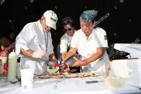 Chef Anita Lo (left) and her team prepare their dish at the James Beard Foundation's Chefs & Champagne fundraiser honoring John Besh, at Wolffer Estate Vineyard in Sagaponack, N.Y