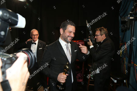 """Alexander Dinelaris is seen backstage with his award for best picture for """"Birdman"""" at the Oscars, at the Dolby Theatre in Los Angeles"""