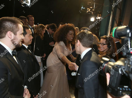 Oprah Winfrey, left, and Graham Moore are seen backstage at the Oscars, at the Dolby Theatre in Los Angeles