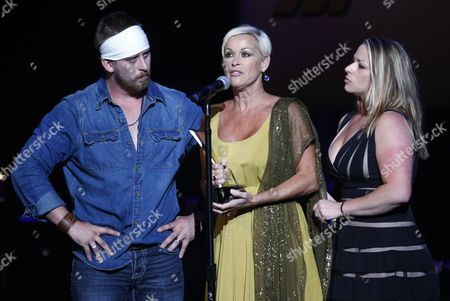 Lorrie Morgan, center, accepts the Pioneer Award for her late husband, Keith Whitley, with her son Jesse Keith Whitley, left, and daughter Morgan Gaddis at the ACM Honors at the Ryman Auditorium on in Nashville, Tenn