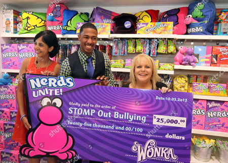 "Nick Cannon, center, joins Natasha Madan, Wonka Marketing Manager, left, Ross Ellis, founder and CEO of STOMP Out Bullying, and Wonka to celebrate NERDS Unite!"", an anti-bullying movement, and present $25,000 to STOMP Out Bullying at Dylan's Candy Bar on in Los Angeles. October is National Bullying Prevention Awareness Month"