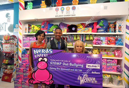 "Nick Cannon, center, joins Natasha Madan, Wonka Marketing Manager, left, Ross Ellis, founder and CEO of STOMP Out Bullying, and Wonka to celebrate 'NERDS Unite!"", an anti-bullying movement, and present $25,000 to STOMP Out Bullying at Dylan's Candy Bar on in Los Angeles. October is National Bullying Prevention Awareness Month"
