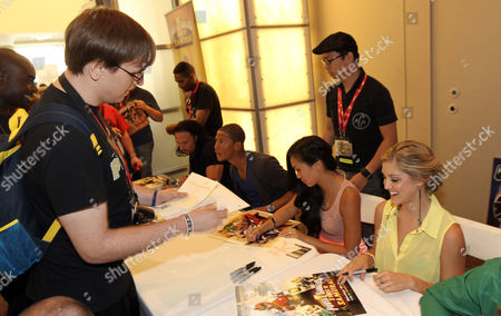 """Stock Image of From left, """"Power Rangers Super Samurai"""" cast members Rick Medina, Najee De-Tiege, Erika Fong, Brittany Pirtle sign autographs for fans at the Power Morphicon Convention 2012, on in Pasadena, Calif"""