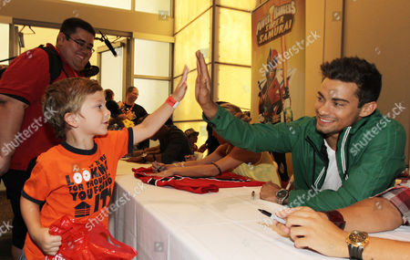 """Power Rangers Super Samurai"""" cast member Hector David Jr., right, greets a young fan while signing autographs at the Power Morphicon Convention 2012, on in Pasadena, Calif"""