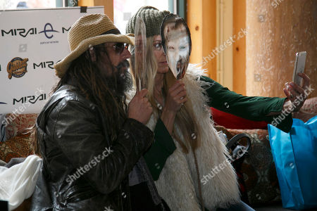 """Rob Zombie, left, and his wife, Sheri Moon Zombie take a selfie while wearing masks of characters from Rob Zombie's Sundance film, """"31"""" at the Toyota Mirai Music Lodge as part of the Sundance Film Festival, in Park City, Utah"""
